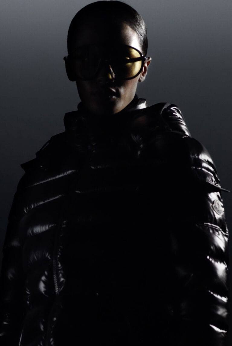 Ein atmosphärisches Bild eines Mannes, der eine schwarze Moncler Daunenjacke mit Sonnenbrille trägt