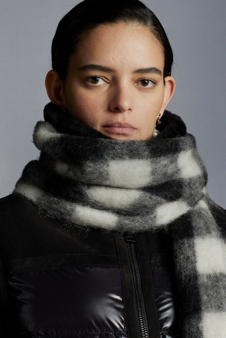 A woman wearing a black Moncler down jacket with a Crafting Knits scarf
