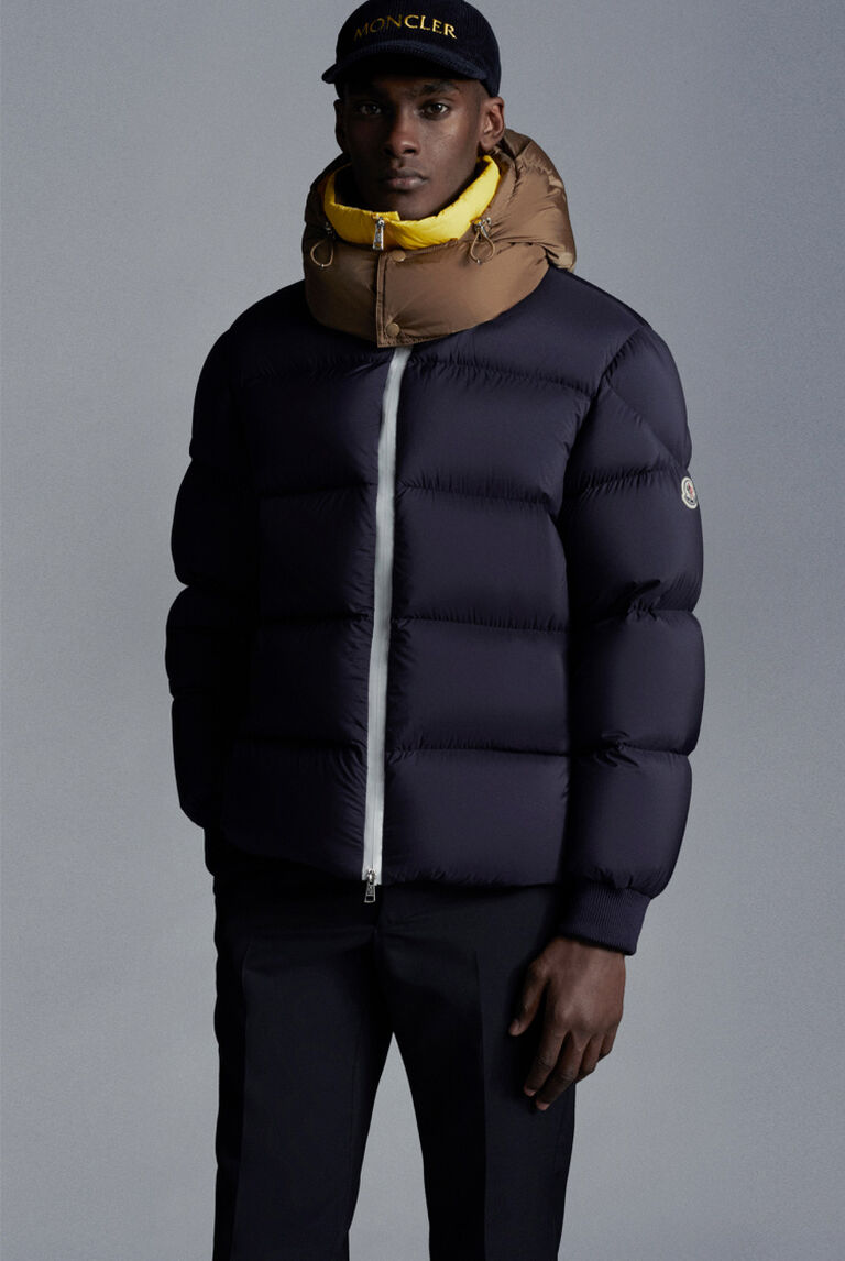 A man wearing a navy Moncler down jacket from the Climbing Kingdoms Collection