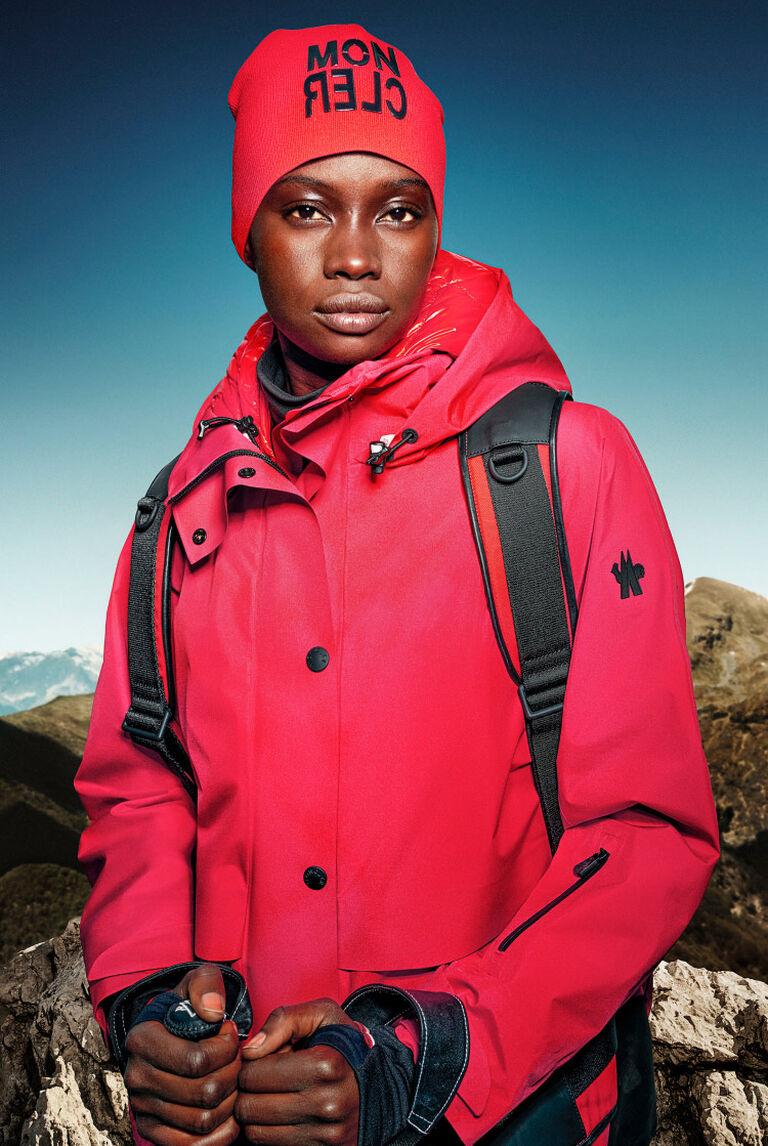 Eine Frau, die eine rote Moncler Daunenjacke mit einer roten Beanie trägt
