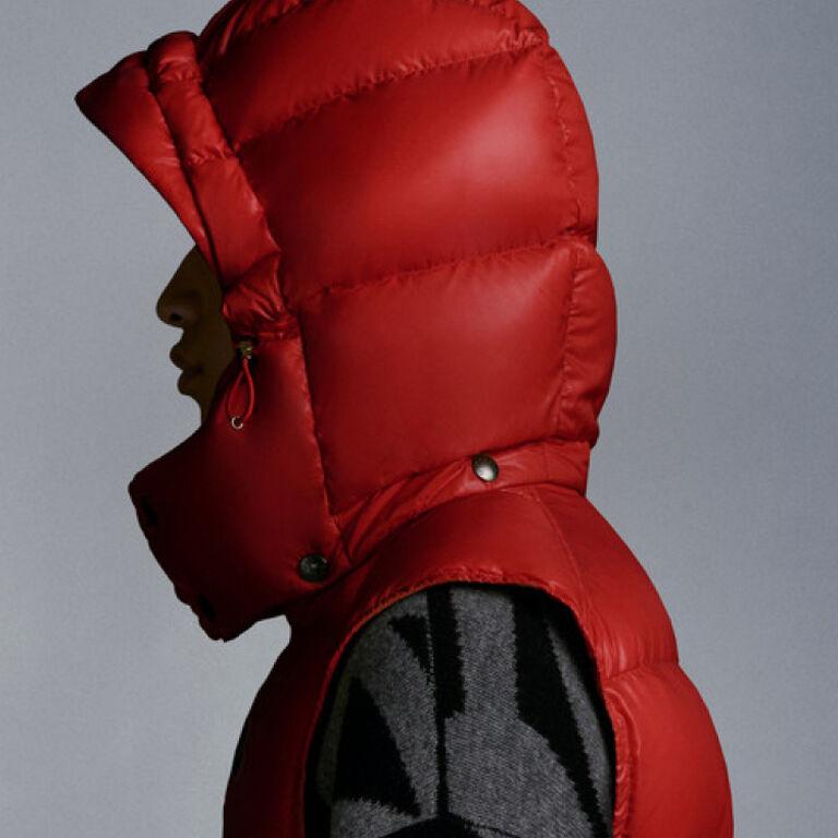 Primo piano di un uomo che indossa un gilet Moncler rosso con cappuccio