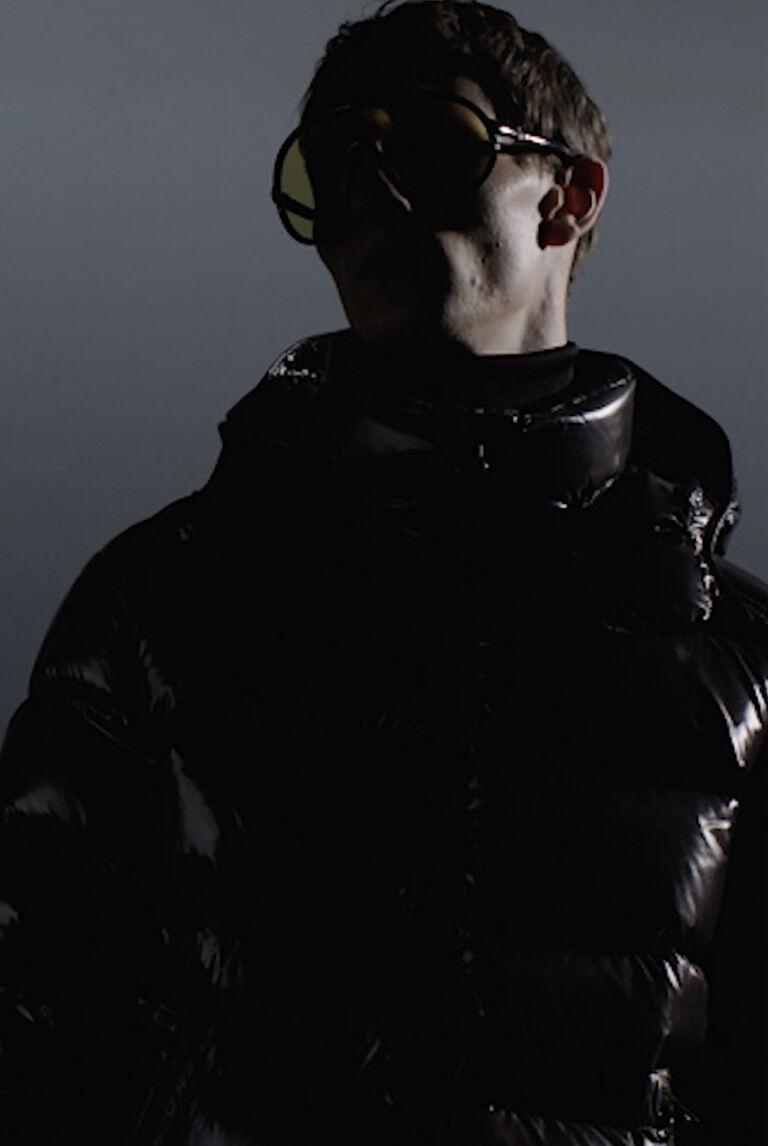 Un'immagine suggestiva di un uomo che indossa occhiali da sole e un piumino nero firmato Moncler