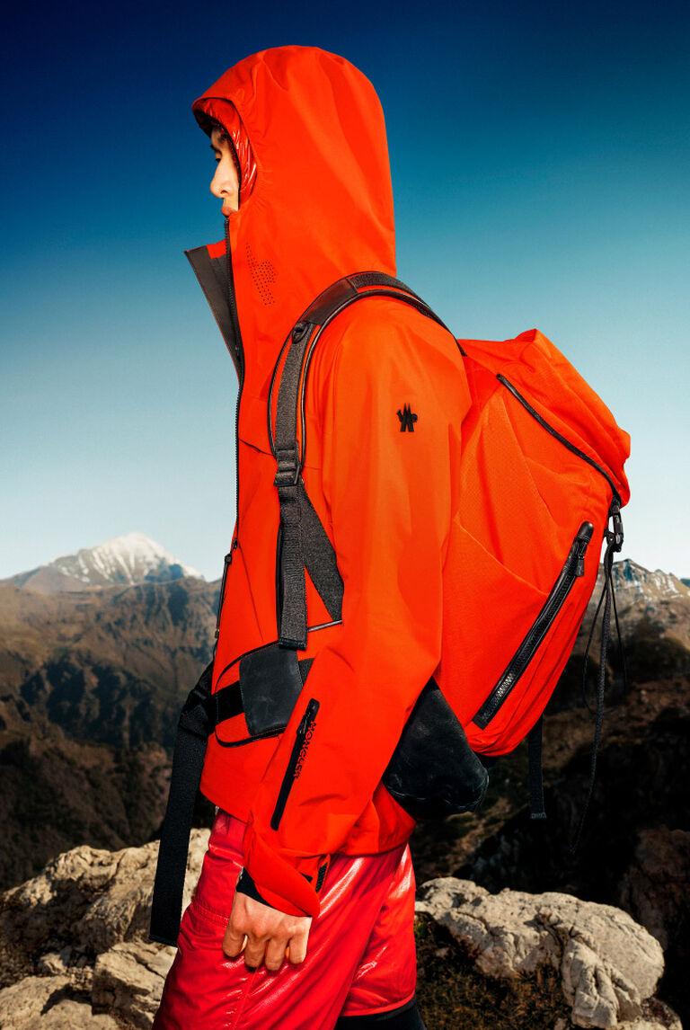 Un uomo che indossa un giubbotto Moncler arancione e uno zaino Moncler arancione
