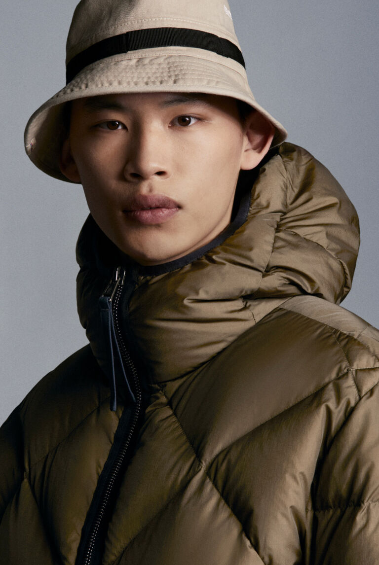 Close-up of a man wearing a beige TREKKING GINZA down jacket by Moncler