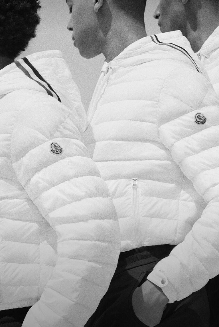 Three men wearing white Moncler down jackets