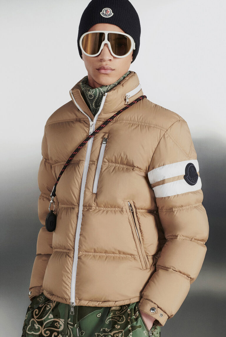 A man wearing a Moncler hooded jacket and beige trousers