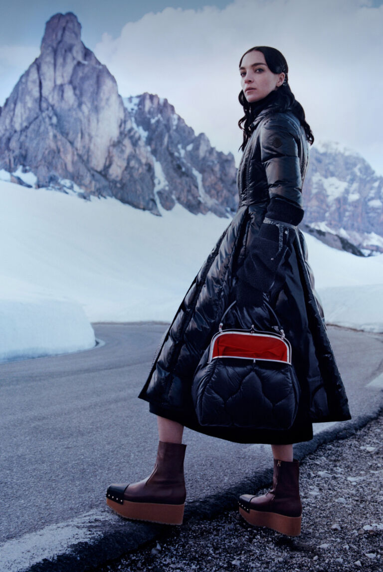 A woman wearing a black Moncler down coat from the 2 MONCLER 1952 WOMAN collection