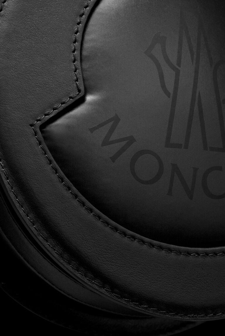 Nahaufnahme eines Moncler-Logos, das auf einer schwarzen Ledertasche aufgenäht ist