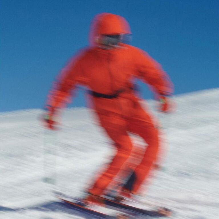Immagine sfocata di uno sciatore con una tuta da neve arancione della collezione Moncler Grenoble