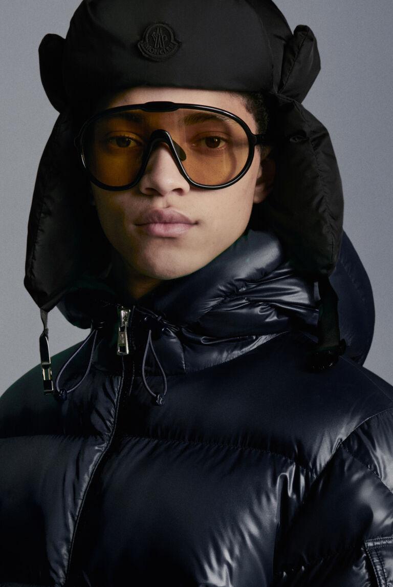 Un hombre con gafas de sol marrones y un plumífero negro Moncler