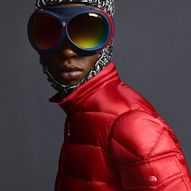 Un uomo che indossa un piumino rosso Moncler Icon e un paio di occhiali blu