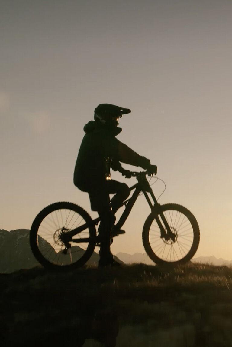 Immagine di copertina del video Moncler Grenoble che ritrae un uomo in bicicletta al tramonto