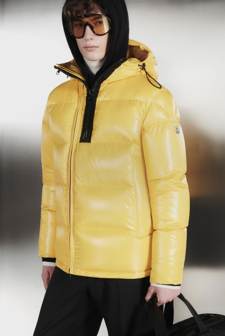 A man with a Moncler yellow down jacket and brown sunglasses