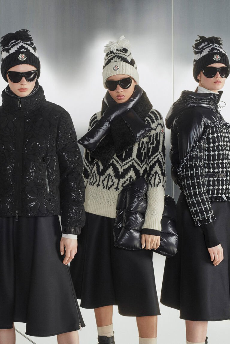 A woman wearing a black Moncler down coat from the CRAFTING KNITS collection