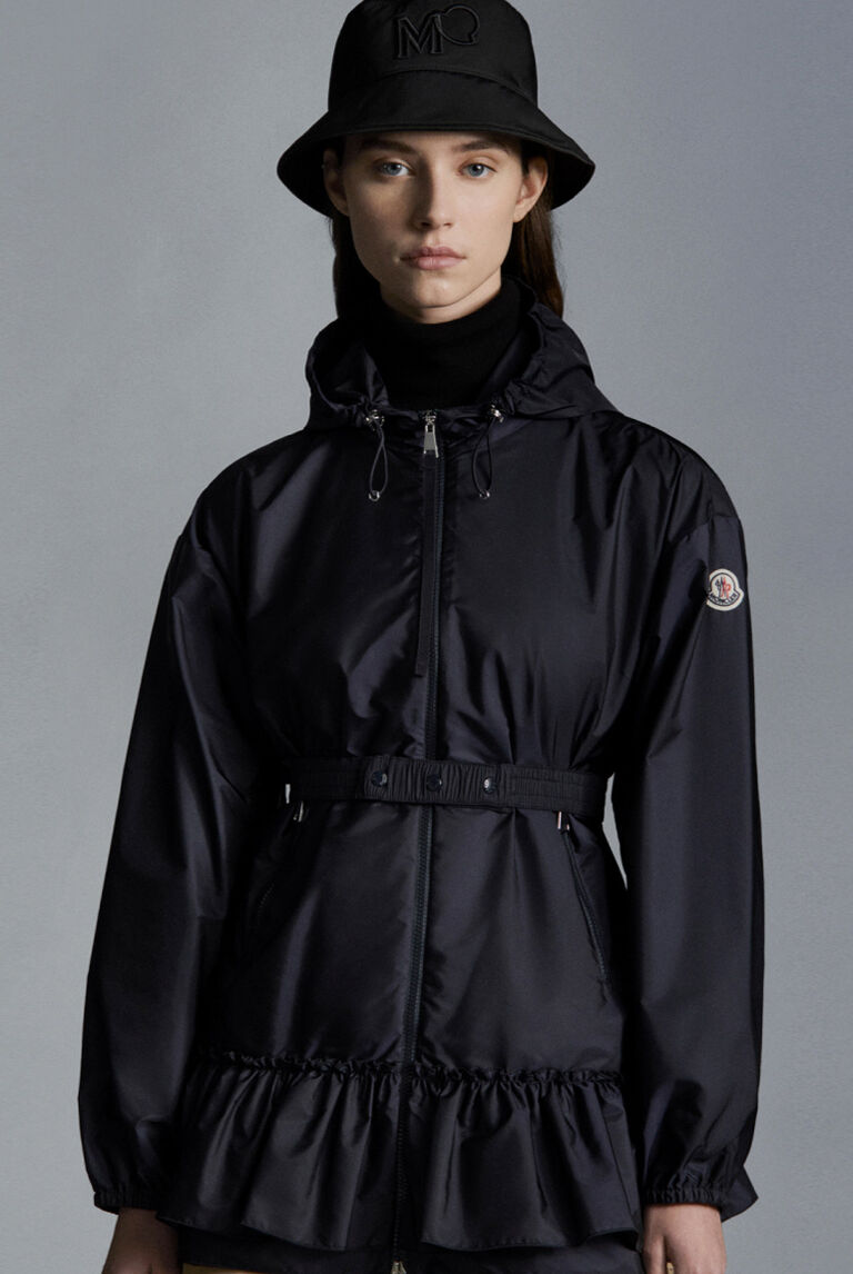A woman with a hat and black Moncler raincoat