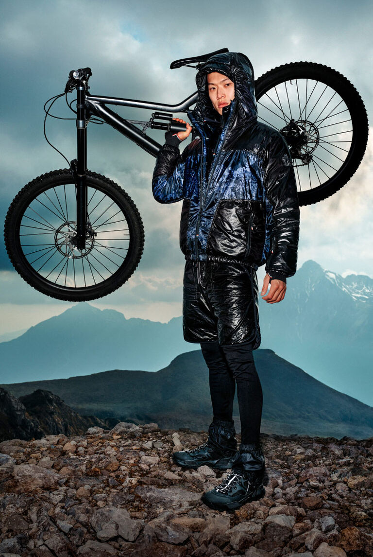 A man wearing a black Moncler Grenoble down jacket while carrying a mountain bike