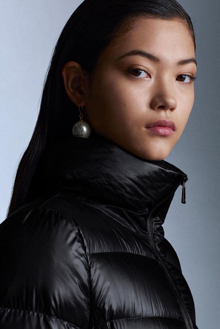 Una mujer con un plumífero negro Moncler de cuello alto