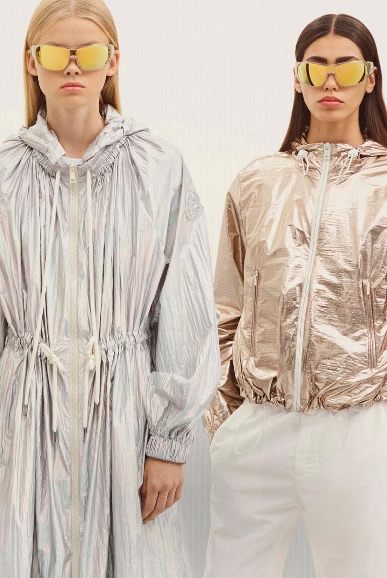 Zwei Damen tragen Moncler Regenmäntel und verspiegelte Sonnenbrillen