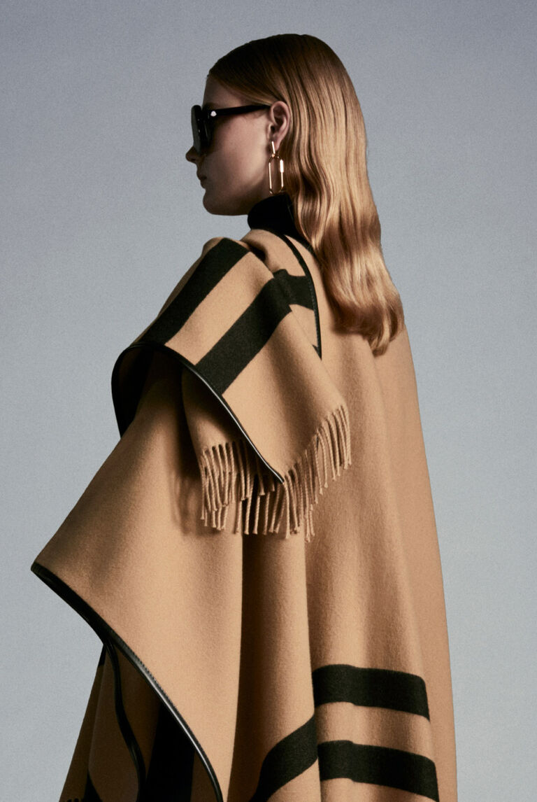 A woman from behind wearing a brown Moncler cape