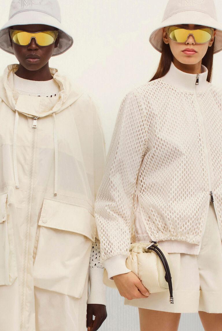 Zwei Damen mit weißen Moncler-Jacken und Mützen