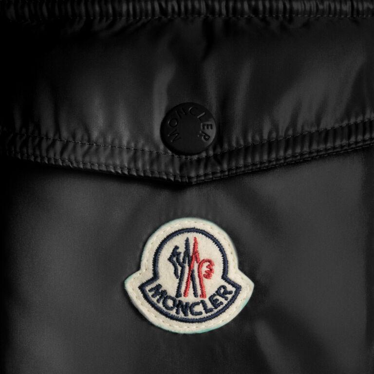 Nahaufnahme des Moncler-Logos auf einer schwarzen Moncler Daunenjacke