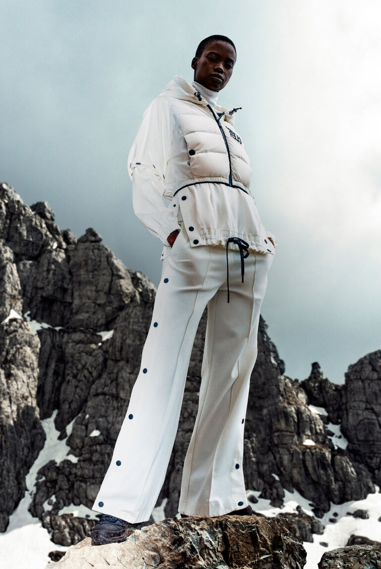 A woman wearing a white ski suit from the Moncler Grenoble Collection