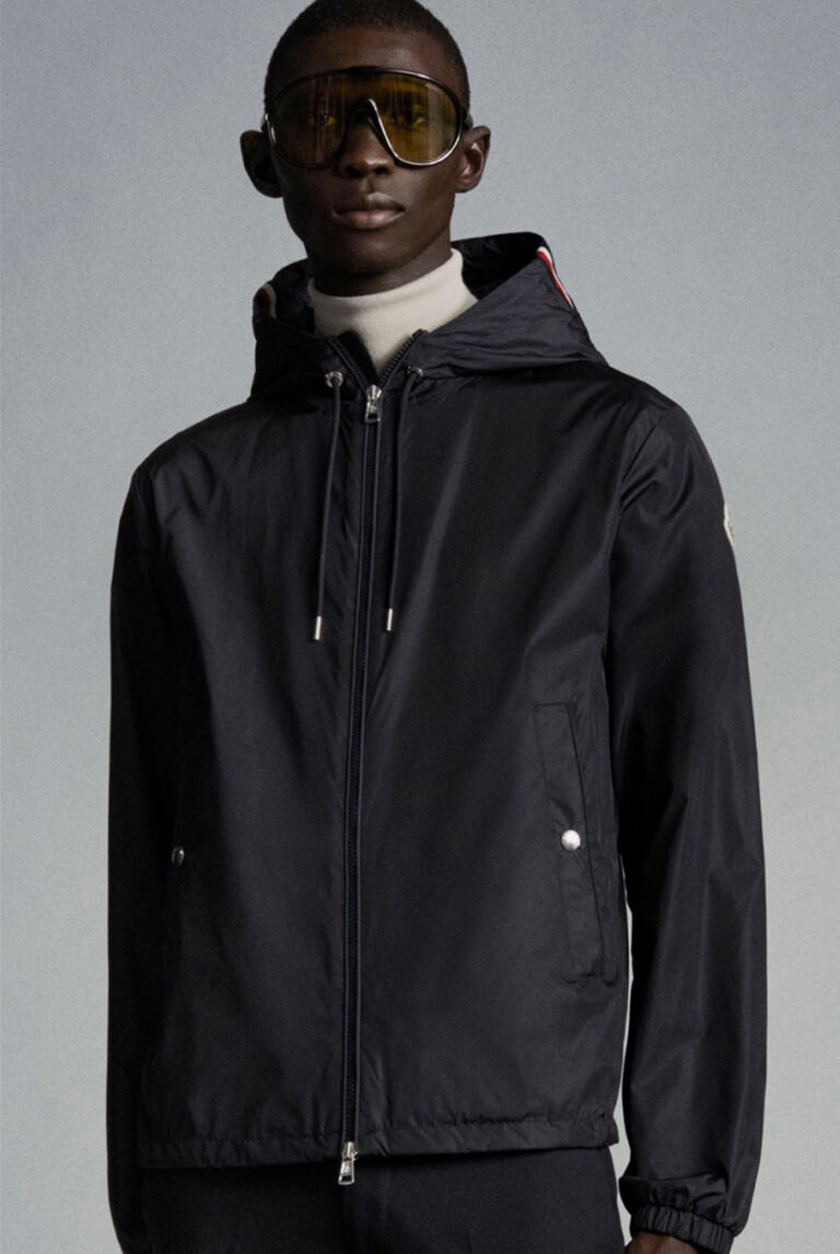 A man in a black Moncler raincoat and sunglasses