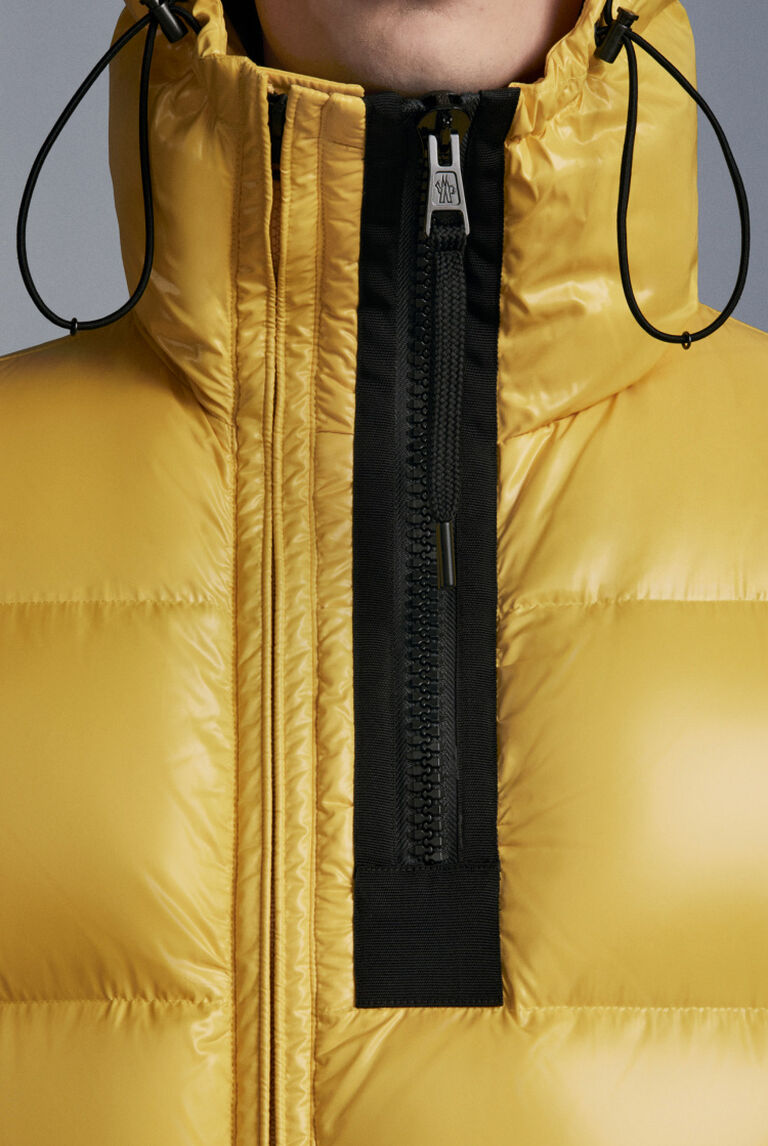 A detail of a yellow Moncler down jacket with black zip