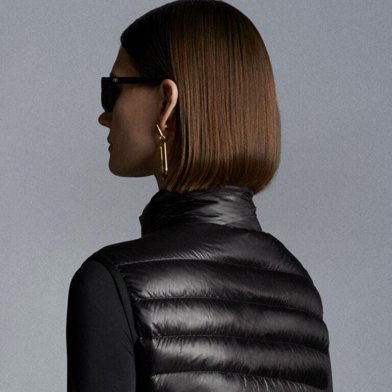 Nahaufnahme einer Frau, die eine schwarze Moncler Daunenjacke mit Sonnenbrille trägt