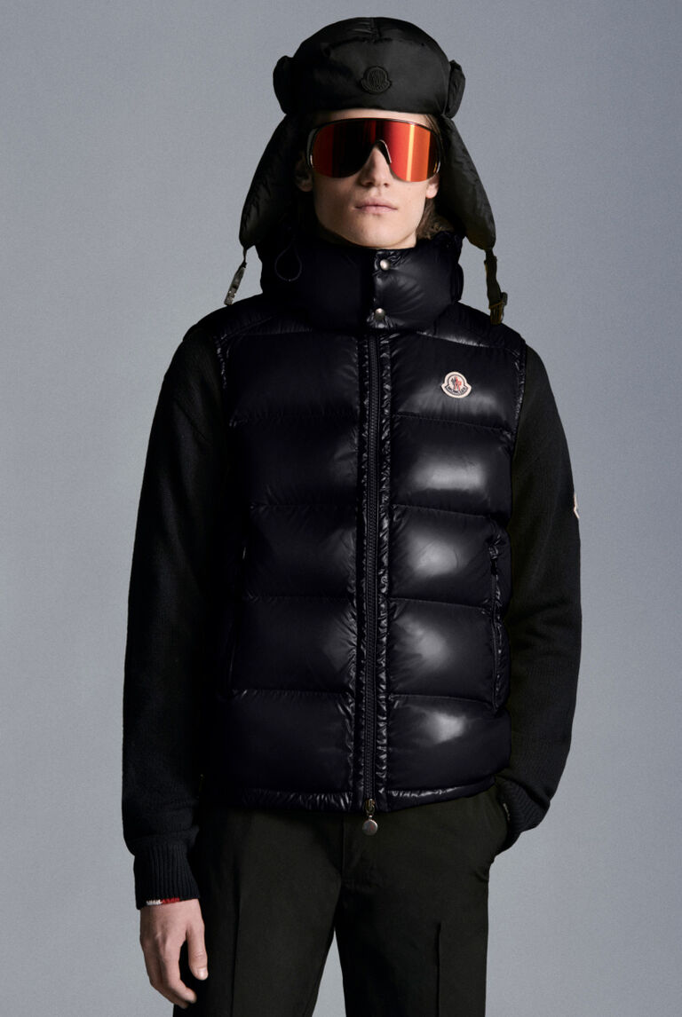 A man wearing a black Moncler short down jacket with mirrored sunglasses