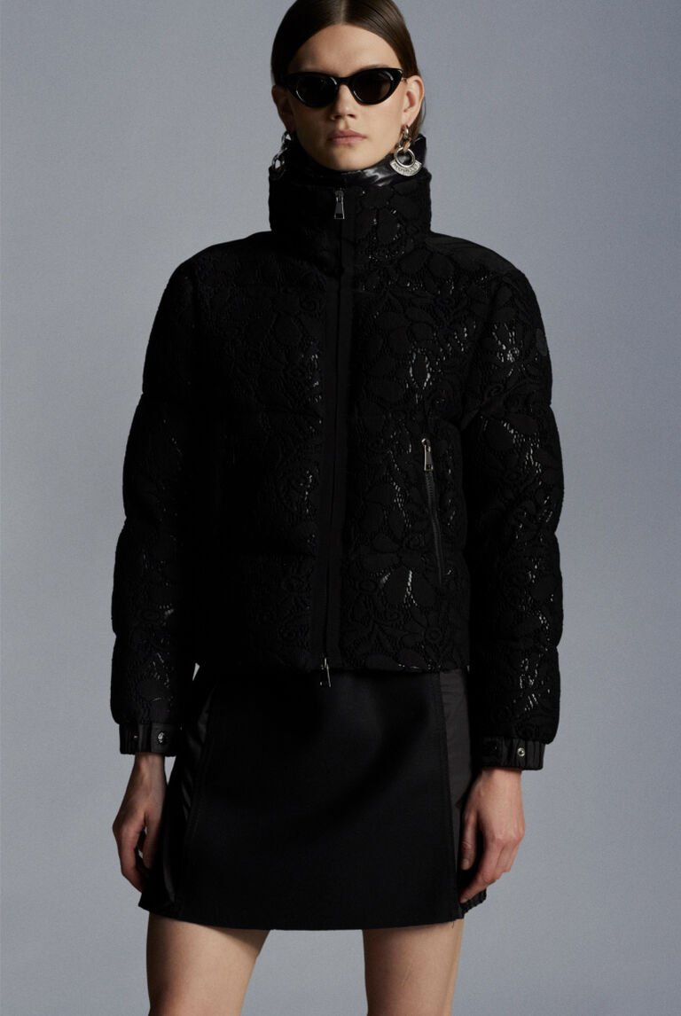 A woman wearing a black Moncler Crafting Knits down jacket with black sunglasses