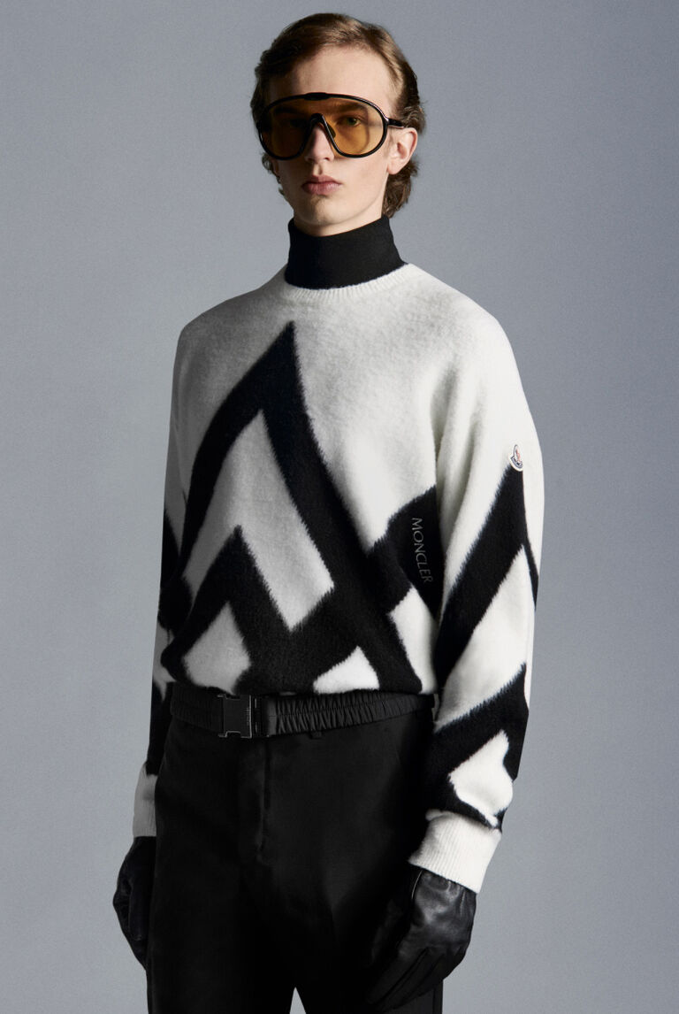 A man wearing a Moncler Vertex Form high neck sweater and brown sunglasses