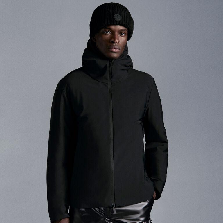 Un uomo che indossa una giacca Moncler nera con un berretto Moncler nero