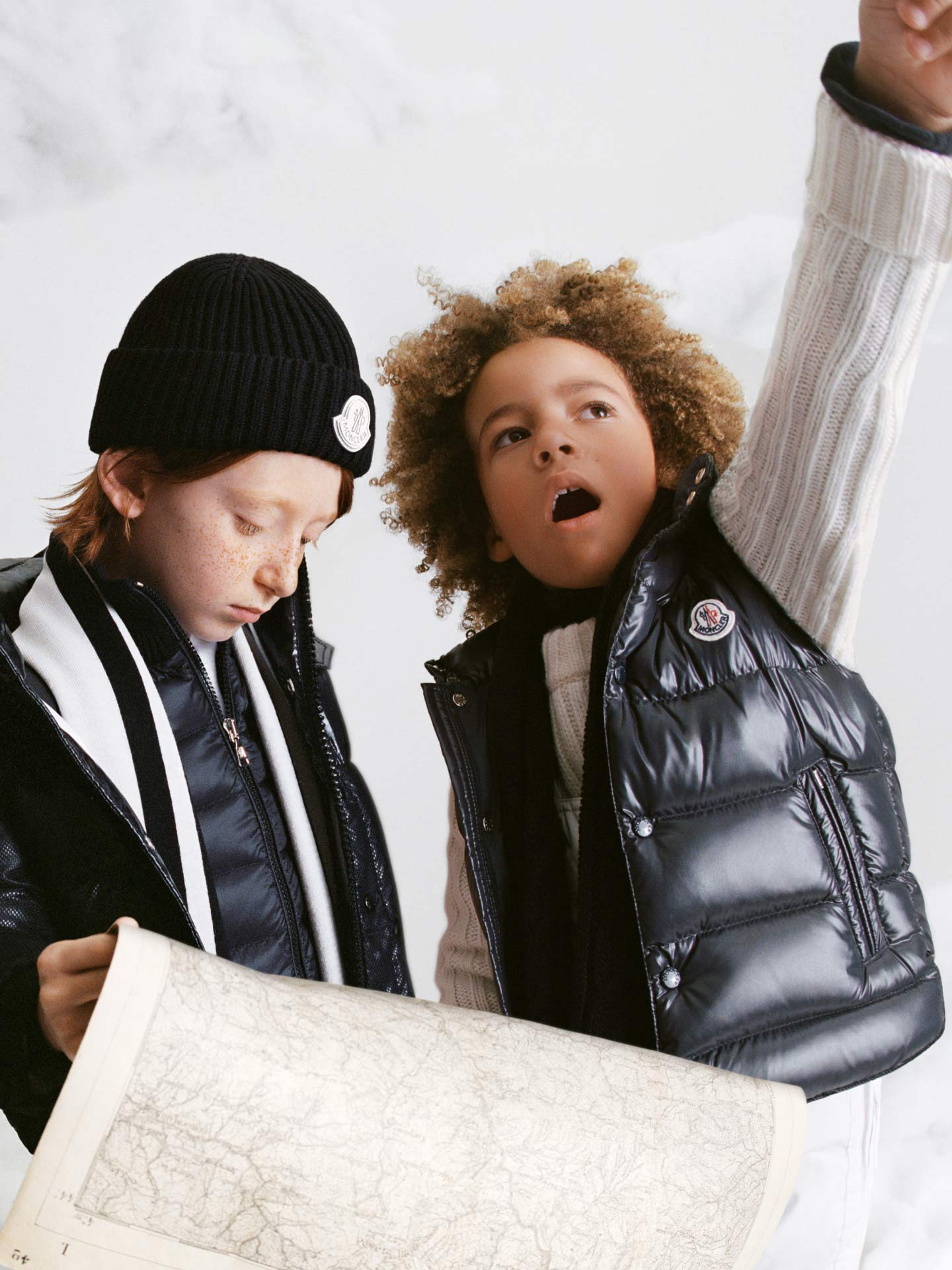 Two boys dressed in a Moncler down jacket and a down gilet for children