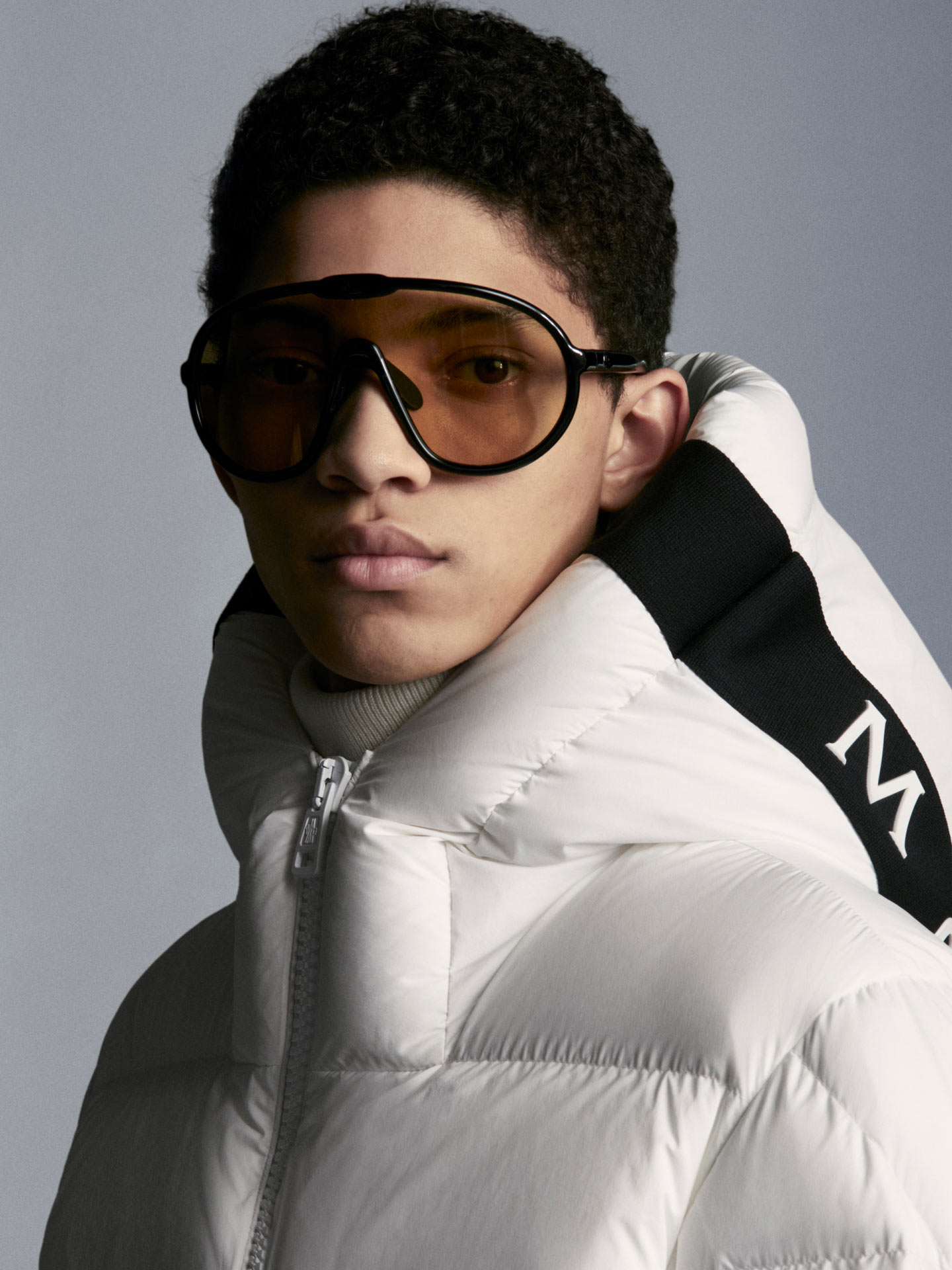 A man wearing a white Moncler down jacket and brown sunglasses