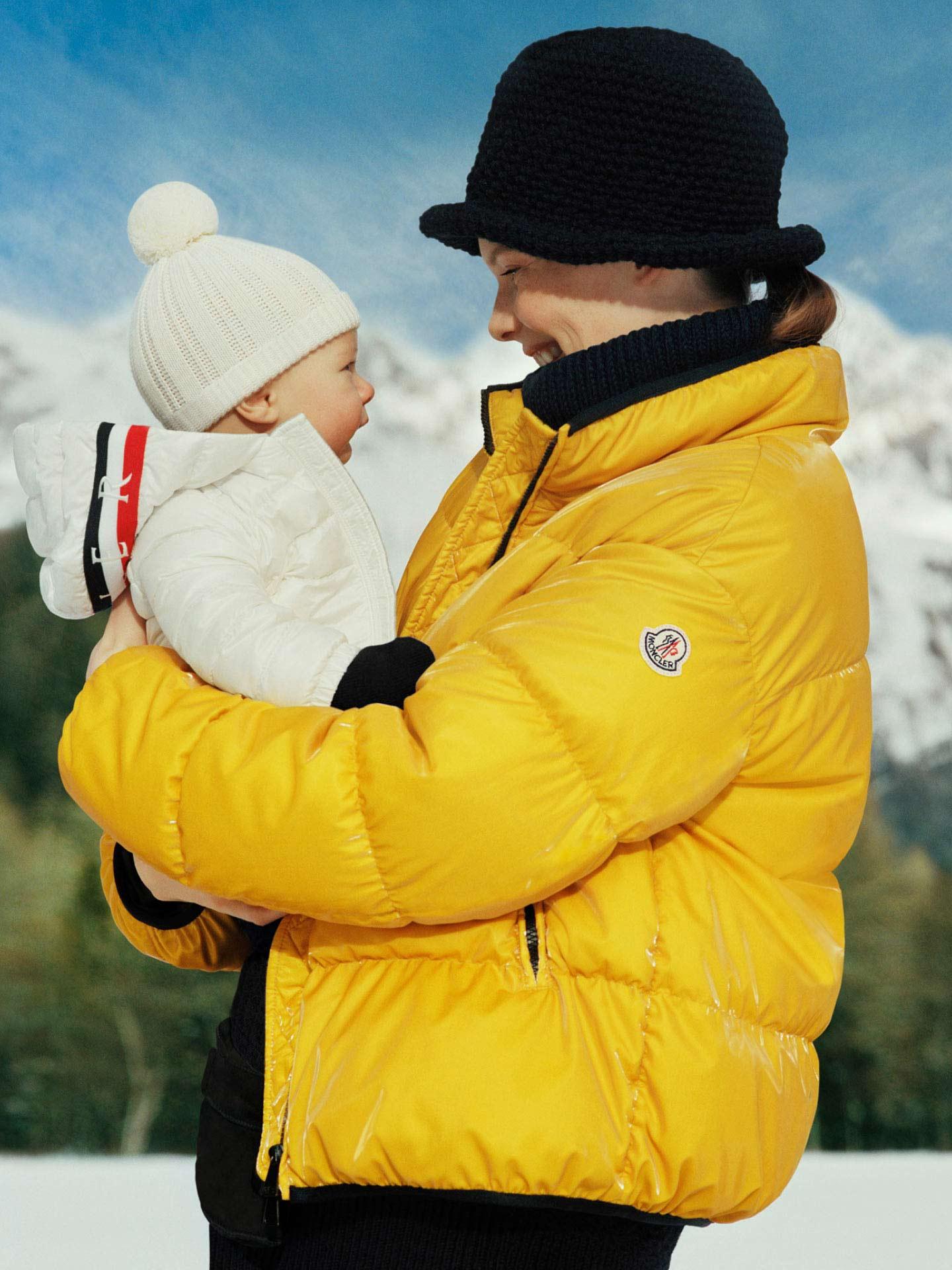Une mère portant un bébé avec une veste blanche Moncler