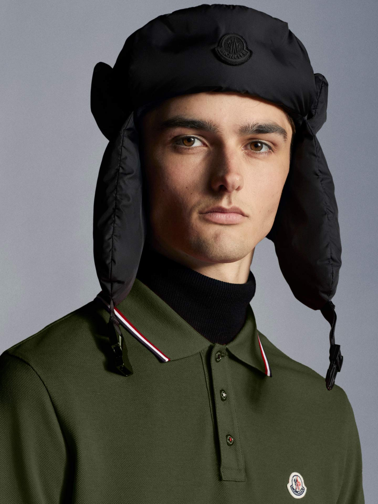 A man wearing a green Moncler polo and a black hat