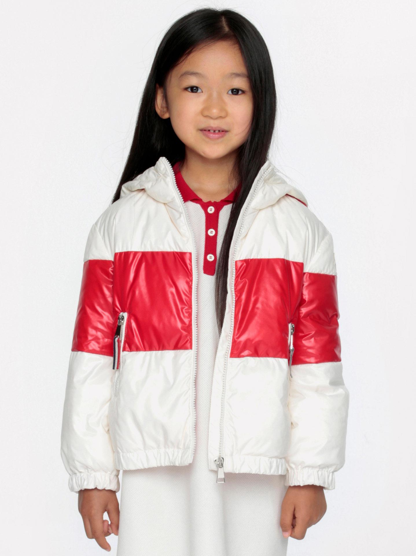 Une fille portant une doudoune Moncler blanche et rouge
