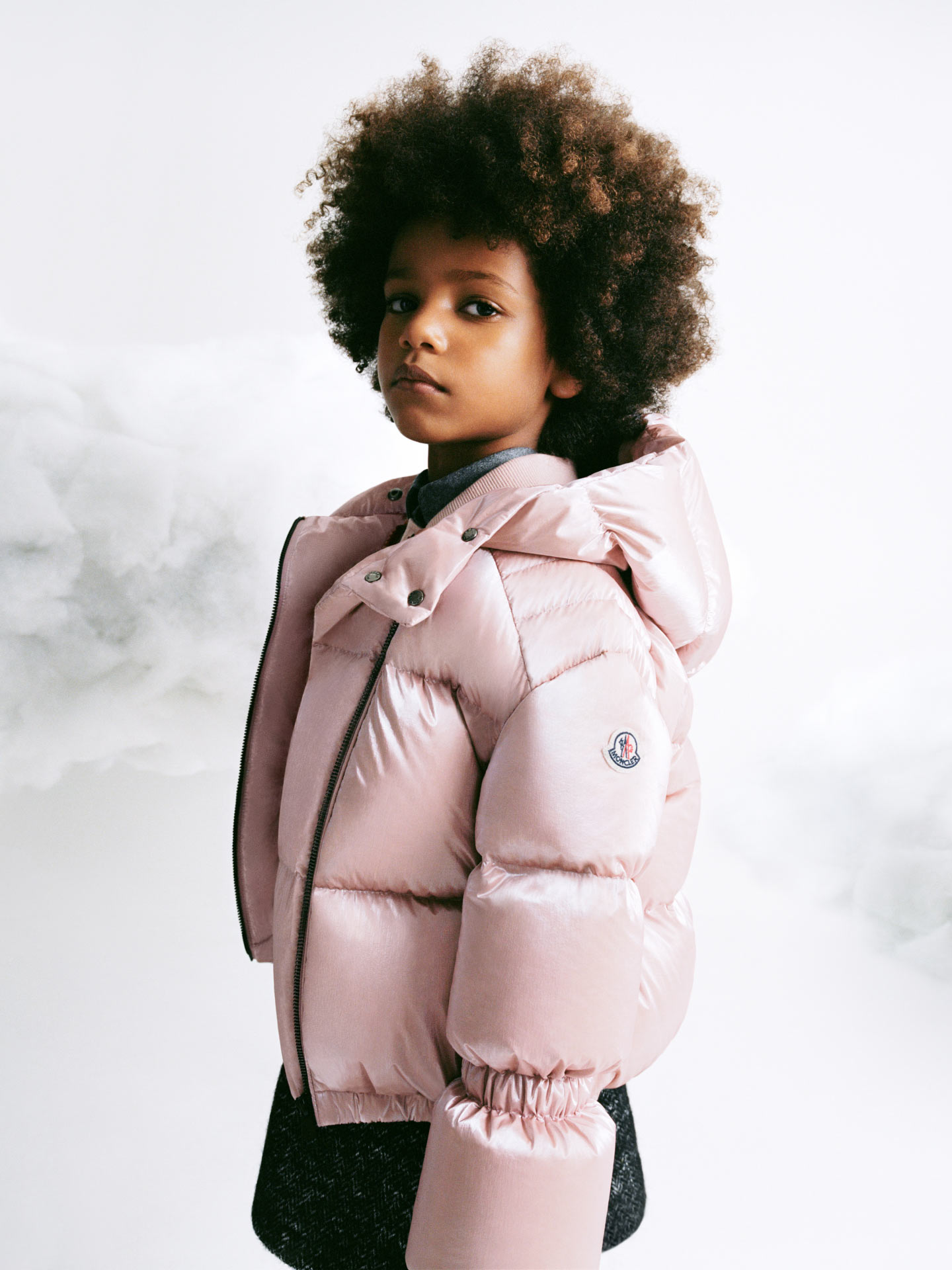 A girl wearing a light pink Moncler down jacket with a black skirt
