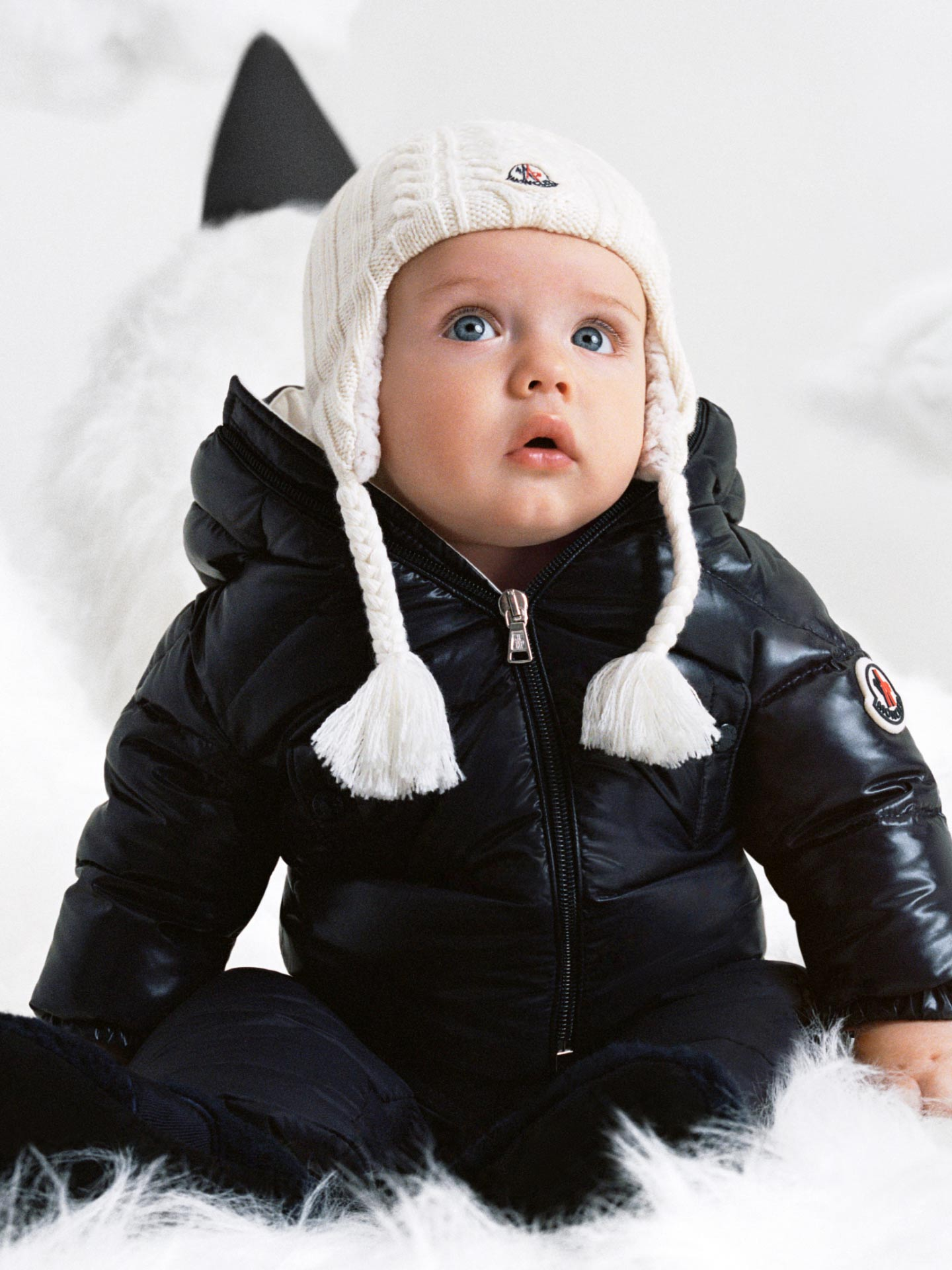 A baby boy dressed in a black Moncler down jacket and a white beanie